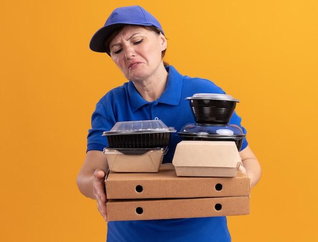Donna di mezza età delle consegne in uniforme blu e cappuccio che tiene scatole per pizza e confezioni di cibo li guarda confusi e scontenti in piedi sopra la parete arancione