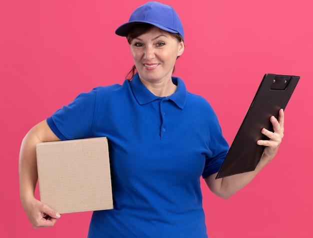 Женщина-доставщик средних лет в синей форме и кепке держит картонную коробку и буфер обмена, глядя вперед, улыбаясь со счастливым лицом, стоящим над розовой стеной