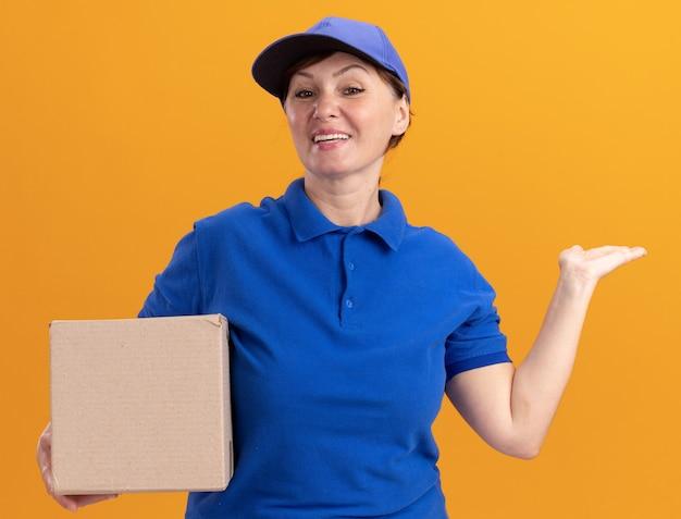 파란색 제복을 입은 중간 세 배달 여자와 오렌지 벽 위에 서있는 행복한 얼굴로 웃는 앞에 팔을보고 뭔가를 제시 골판지 상자를 들고 모자