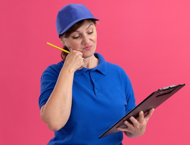 Женщина-доставщик средних лет в синей форме и кепке держит в руках буфер обмена и карандаш, глядя на него с растерянным выражением лица, стоя над розовой стеной