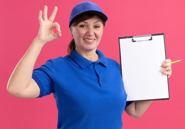 파란색 제복을 입은 중간 세 배달 여자와 분홍색 벽 위에 서있는 확인 서명을 유쾌하게 보여주는 전면을보고 빈 페이지와 클립 보드를 들고 모자