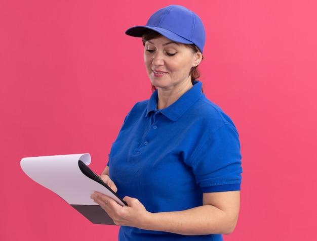 파란색 유니폼과 모자 핑크 벽 위에 서있는 얼굴에 미소로보고 빈 페이지 클립 보드를 들고 중간 세 배달 여자
