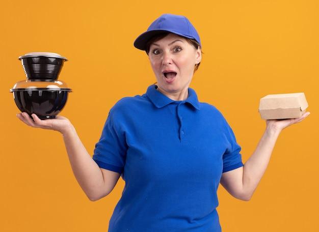 파란색 유니폼과 모자를 들고 앞을보고 음식 패키지를 들고 중간 세 배달 여자는 오렌지 벽 위에 서 놀란 놀라움