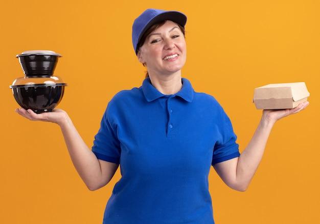 オレンジ色の壁の上に立って幸せで前向きな笑顔の正面を見て食品パッケージを保持している青い制服と帽子の中年配達の女性