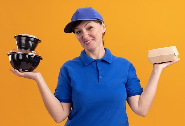 파란색 제복을 입은 중간 세 배달 여자와 오렌지 벽 위에 서있는 전면 행복하고 긍정적 인 미소를보고 음식 패키지를 들고 모자