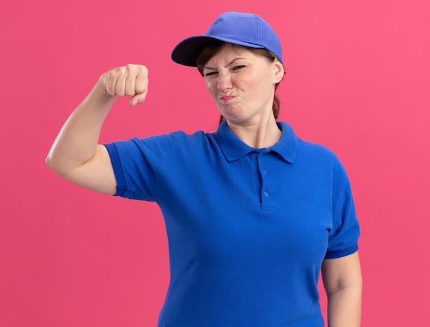 파란색 제복을 입은 중간 세 배달 여자와 분홍색 벽 위에 서서 불쾌한 주먹을 움켜 쥐고있는 정면을보고 모자