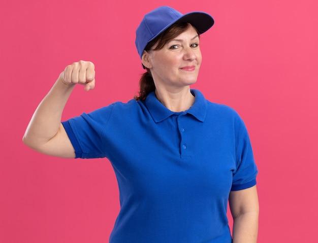 ピンクの壁の上に立って自信を持って笑っているくいしばられた握りこぶしを示す正面を見て青い制服とキャップの中年配達の女性