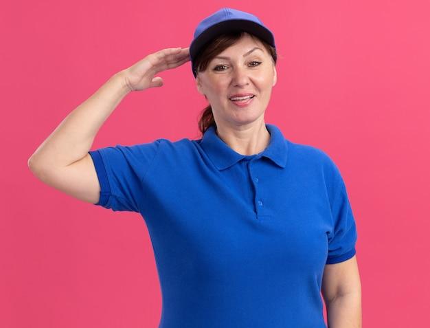 Женщина-доставщик средних лет в синей униформе и кепке, глядя вперед, улыбается, уверенно салютует, стоя над розовой стеной
