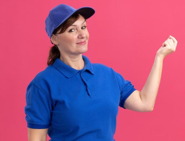 Женщина-доставщик средних лет в синей униформе и кепке смотрит вперед, улыбаясь, делая денежный жест, потирая пальцы в ожидании оплаты, стоя над розовой стеной