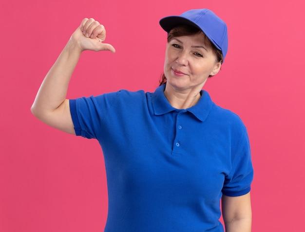 파란색 제복을 입은 중간 세 배달 여자와 분홍색 벽 위에 서있는 자신을 가리키는 자신감있는 표정으로 정면을 바라 보는 모자