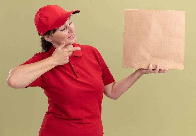 赤い制服を着た中年の配達の女性とそれを人差し指で指している紙のパッケージを保持しているキャップは、緑の壁の上に立って自信を持って笑っています