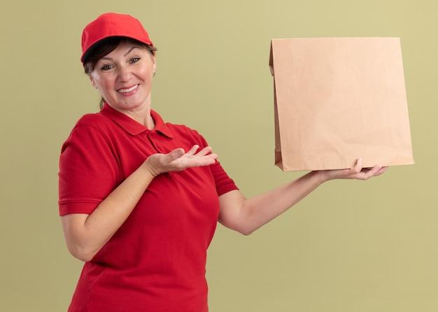 赤い制服を着た中年の配達の女性と紙のパッケージを保持しているキャップは、緑の壁の上に立って自信を持って笑顔の前を見て腕を提示します