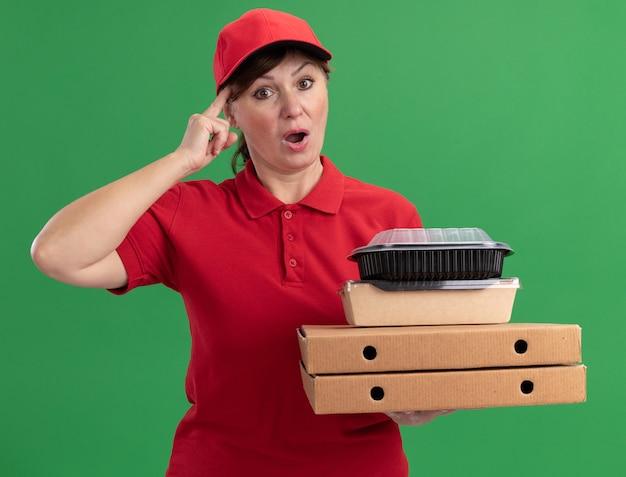 緑の壁の上に立って混乱している正面を見てピザの箱と食品パッケージを保持している赤い制服と帽子の中年配達の女性