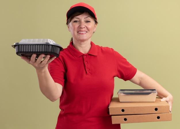 緑の壁の上に立って自信を持って笑顔で正面を見てピザの箱と食品パッケージを保持している赤い制服と帽子の中年配達の女性