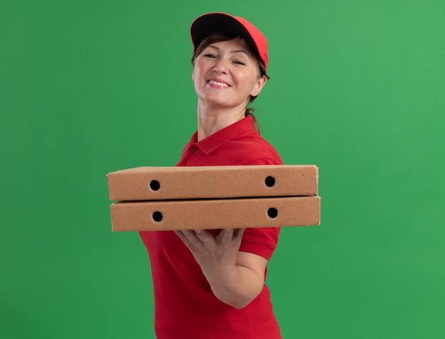 緑の壁の上に立っている幸せそうな顔で笑顔で正面を見てピザの箱を保持している赤い制服と帽子の中年配達の女性