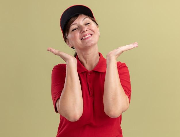 緑の壁の上に立って手を上げて幸せで前向きな笑顔を正面から見ている赤い制服とキャップの中年配達の女性