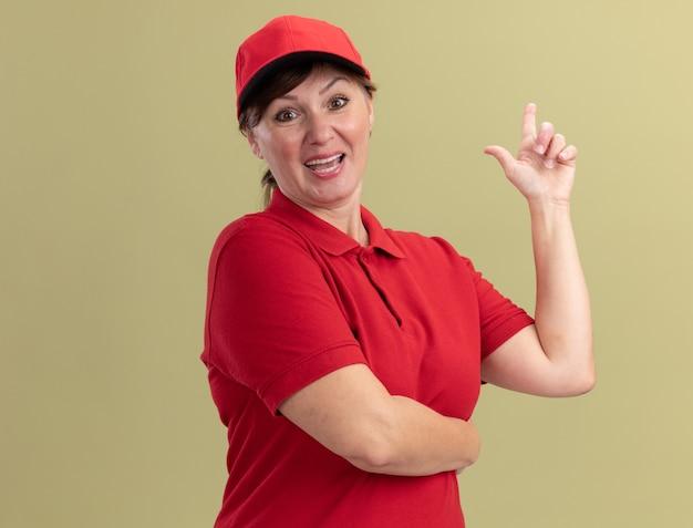 Женщина-доставщик средних лет в красной униформе и кепке, глядя вперед, уверенно улыбается, показывая указательный палец, имеющий новую отличную идею, стоящий над зеленой стеной