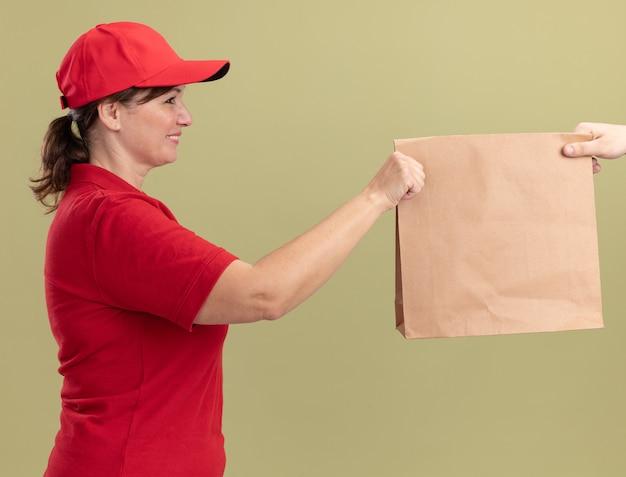 Donna di mezza età delle consegne in uniforme rossa e cappuccio che dà il pacchetto di carta a un cliente che sorride amichevole che sta sopra la parete verde