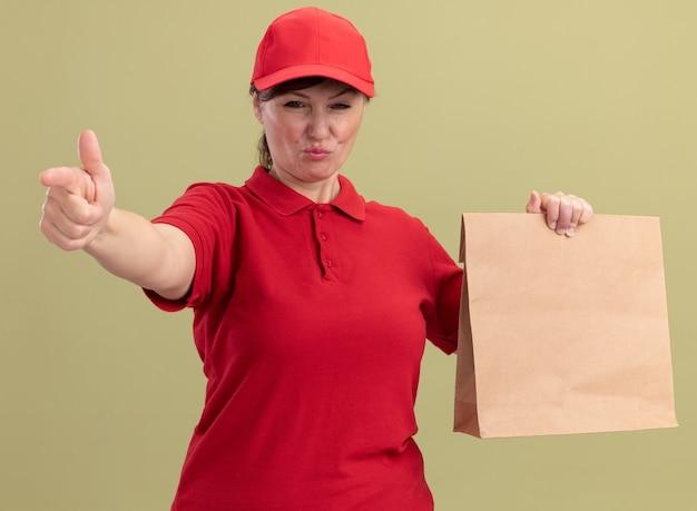 Donna di mezza età delle consegne in uniforme rossa e cappuccio che dà pacchetto di carta guardando davanti con espressione seria e sicura che punta con il dito indice davanti in piedi sopra la parete verde