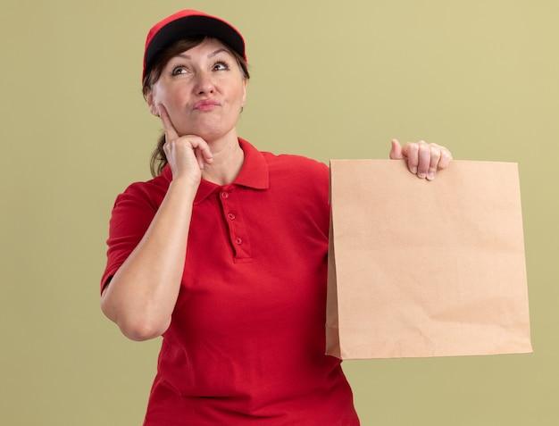 Donna di consegna di mezza età in uniforme rossa e cappuccio che dà pacchetto di carta che osserva in su con espressione pensierosa sul pensiero del viso in piedi sopra la parete verde