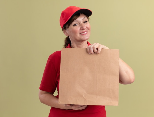Middle aged delivery woman in red uniform and cap holding paper package looking at front smiling confident standing over green wall