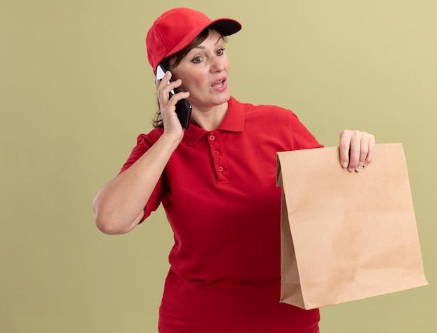 Donna di mezza età delle consegne in uniforme rossa e cappuccio che tiene il pacchetto di carta parlando al telefono cellulare cercando confuso in piedi sopra la parete verde