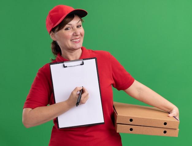 Donna di mezza età delle consegne in uniforme rossa e cappuccio che tiene scatole per pizza e appunti con pagine vuote e penna guardando davanti sorridente chiedendo la firma in piedi sopra il muro verde