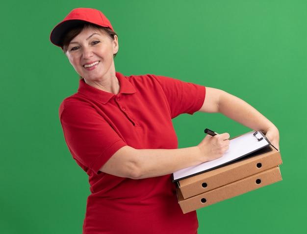 Donna di mezza età delle consegne in uniforme rossa e cappuccio che tiene scatole per pizza e appunti con pagine vuote che scrivono con la penna guardando la parte anteriore sorridente con la faccia felice in piedi sopra la parete verde