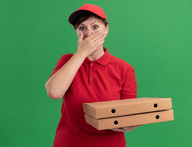 Middle aged delivery woman in red uniform and cap holding pizza boxes looking at front being shocked covering mouth with hand standing over green wall