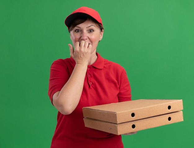 Donna di mezza età delle consegne in uniforme rossa e cappuccio che tiene le scatole per pizza guardando le unghie mordaci nervose davanti in piedi sopra la parete verde