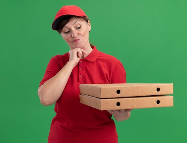 Donna di mezza età delle consegne in uniforme rossa e cappuccio che tiene le scatole per pizza guardandole con espressione pensierosa pensando in piedi sopra la parete verde