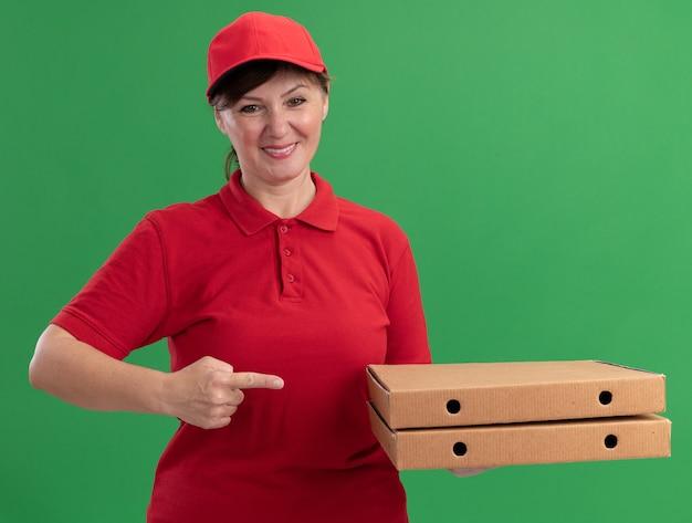 Donna di consegna di mezza età in uniforme rossa e cappuccio che tiene le scatole per pizza che punta con il dito indice alle scatole che sorridono fiducioso in piedi sopra la parete verde