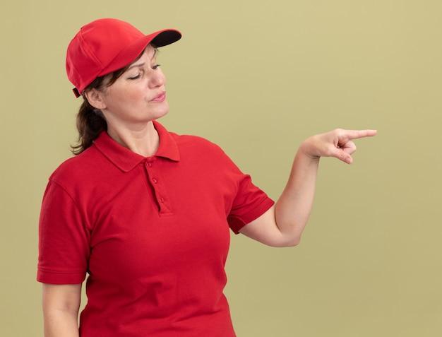 Donna di mezza età delle consegne in uniforme rossa e berretto da parte con la faccia seria che punta il dito indice sul lato in piedi sopra la parete verde