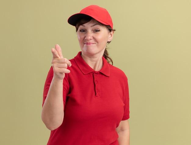 Donna di consegna di mezza età in uniforme rossa e berretto che sembra fiducioso che punta con il dito indice davanti in piedi sopra la parete verde