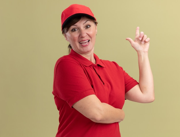 Donna di mezza età consegna in uniforme rossa e berretto guardando davanti sorridente fiducioso che mostra il dito indice avente una nuova grande idea in piedi sopra la parete verde