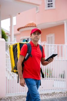 Доставщик средних лет смотрит в сторону, держит в руках термосумку и планшет. кавказский курьер в красной рубашке и кепке идет по улице и доставляет заказ. служба доставки и почтовая концепция