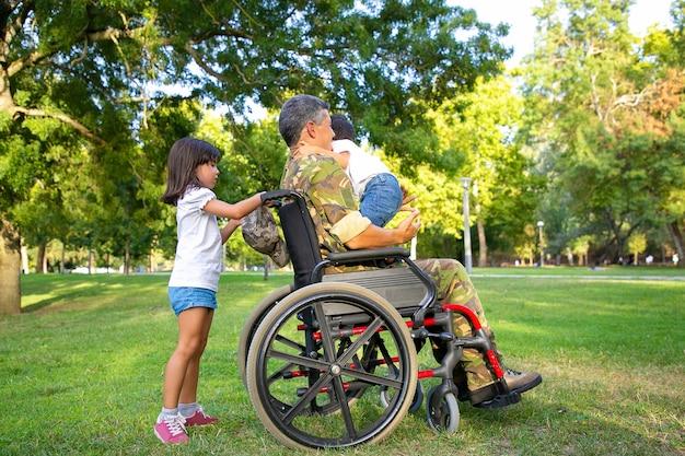 公園で2人の子供と一緒に歩いている中年の障害者の軍のお父さん。車椅子のハンドルを持っている女の子、お父さんの膝の上に立っている男の子。戦争または障害の概念のベテラン