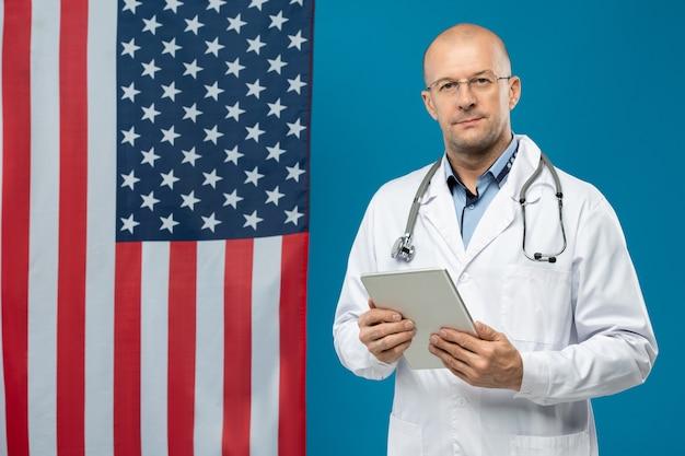카메라 앞에서 별과 줄무늬 copyspace에 서있는 동안 태블릿을 사용하는 화이트 코트와 안경의 중간 세 의사