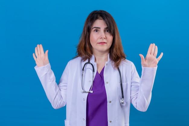 中年の医者が白いコートを着て、青い壁に混乱して探している降伏で手を上げる聴診器で