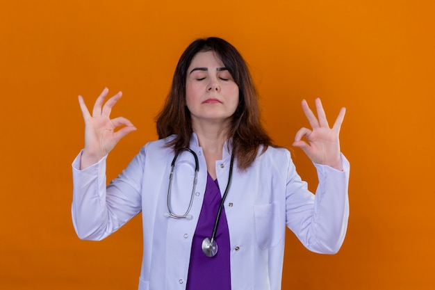 中年の医者が白いコートを着て、聴診器でリラックスしてオレンジ色の壁に指で瞑想ジェスチャーをして目を閉じて笑顔
