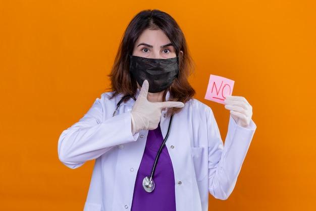 Medico di mezza età che indossa camice bianco in maschera protettiva nera e con stetoscopio tenendo la carta promemoria senza la parola che punta con il dito