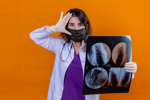 Middle aged doctor wearing white coat in black protective facial mask and with stethoscope holding x-ray of lungs looking surprised with hand near head over orange wall