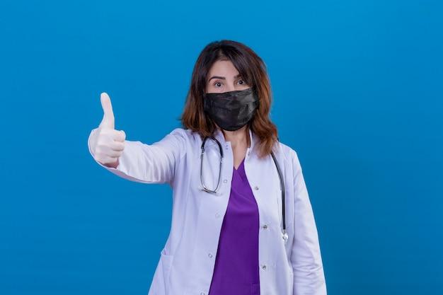 Medico di mezza età che indossa camice bianco in maschera protettiva nera e con lo stetoscopio che sembra positivo mostrando i pollici in su sopra la parete blu