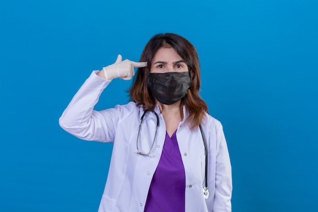 Middle aged doctor wearing white coat in black protective facial mask and with stethoscope making finger pistol or gun gesture near temple over blue wall