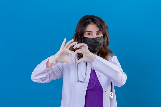 Middle aged doctor wearing white coat in black protective facial mask and with stethoscope making romantic heart gesture over chest