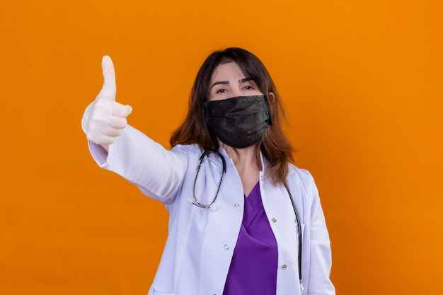 Middle aged doctor wearing white coat in black protective facial mask and with stethoscope positive and happy showing thumbs up over orange wall