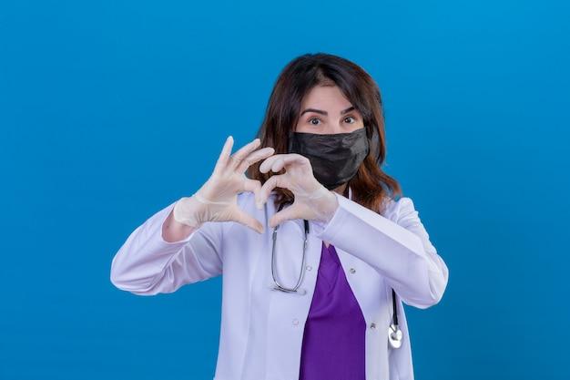 Доктор средних лет в белом халате в черной защитной маске для лица и со стетоскопом, делающим романтичный жест сердца над грудью