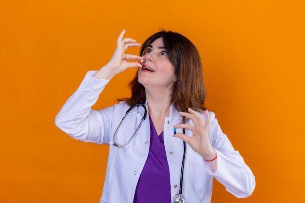 Middle aged doctor wearing white coat and with stethoscope holding pills in hands trying to take a pill over orange wall