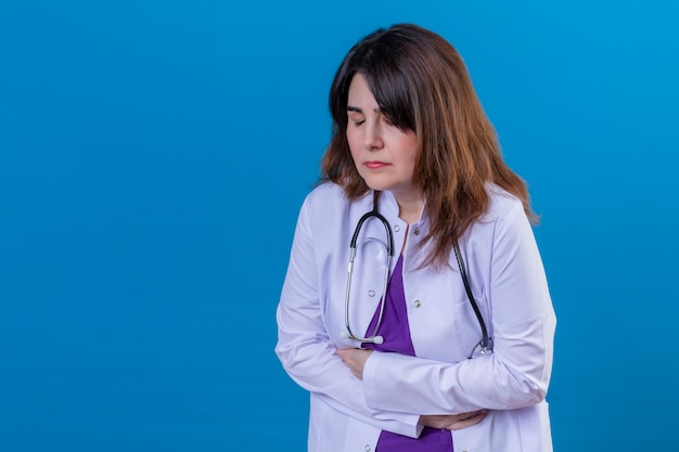 Middle aged doctor wearing white coat and with stethoscope looking unwell touching stomach suffering from pain over blue wall