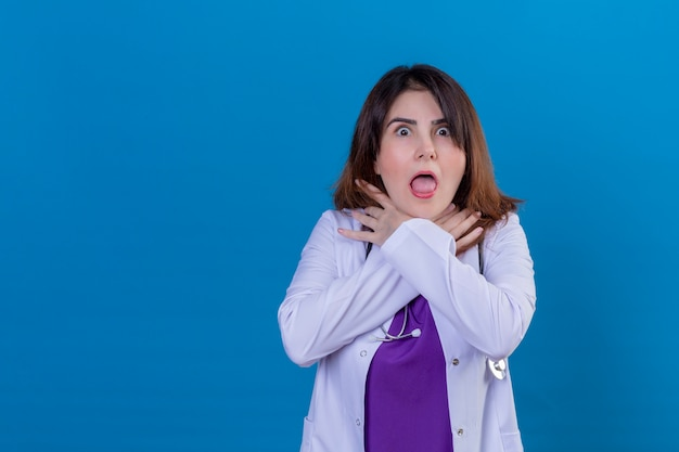 Middle aged doctor wearing white coat and with stethoscope shouting and suffocate because painful strangle over blue wall